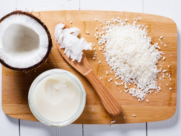 Whole and broken coconut with grated cocont flakes and coconut oil or butter.