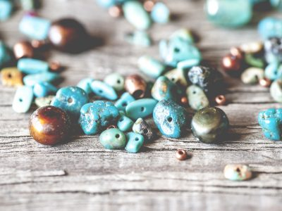 Macro view of a group of vibrant turquoise and copper beads on rustic wooden surface