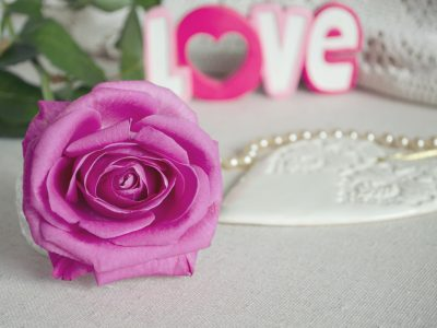 Vintage style ornamental wooden white heart, with pink rose buds, word LOVE and necklace on textile surface, shabby chic and romantic. Copy space