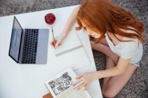 Charming young woman doing homework