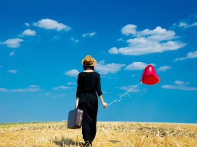 young woman with suitcase and balloon