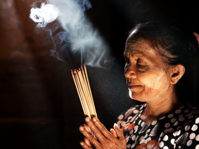 Old wrinkled traditional Asian woman praying with incense sticks inside a temple, low light with smoke and beautiful natural sunlight, Myanmar