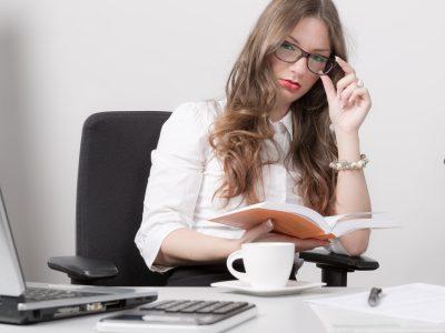 Junge Frau mit Brille am Schreibtisch mit Buch