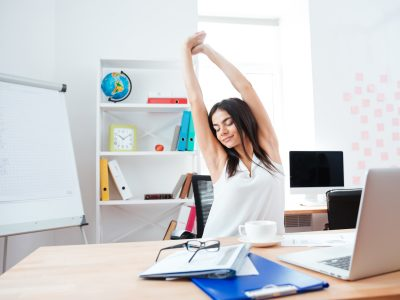 Beautiful businesswoman stretching hands in office