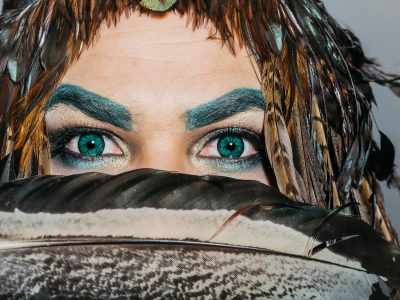 Male face with handsome eye with decorative contact lens of emerald green color eyebrow and eyeshadow makeup big brown feather near and head decorated with feathers closeup