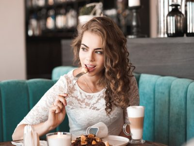 Beautiful blonde woman 20-24 year eating brownie dessert and drinking coffee in cafe. Looking away.