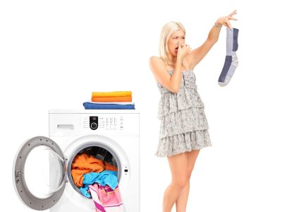 A housewife holding a male sock and her nose next to a washing m