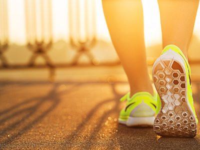 Runner woman feet running on road closeup on shoe.