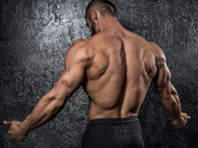 Man showing his muscular back against conctete wall