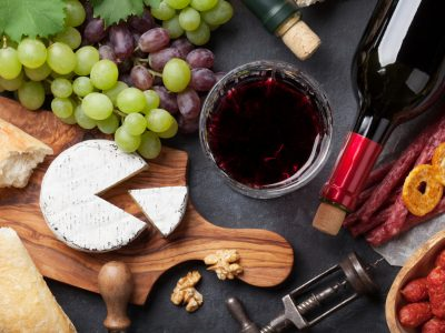 Red and white wine, grape, cheese and sausages over stone table. Top view
