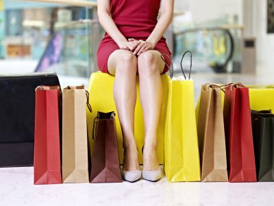 young woman's legs and colorful shopping bags