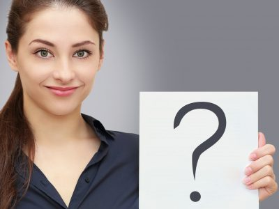 Business woman holding blank with request question sign on grey background. Closeup portrait