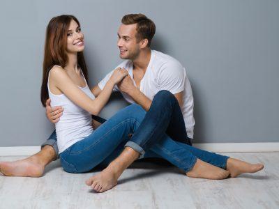 Beautiful young amorous couple, sitting on floor