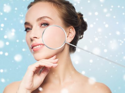 beautiful woman with magnifier on face over snow