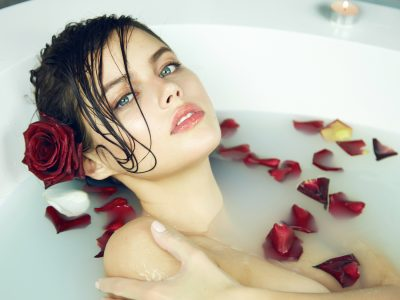 Beautiful young sexy woman with dark hair wet, evening makeup, takes bath with milk and rose petals and candles, beauty salon and spa Valentine's Day.