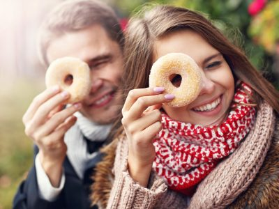 Young couple sitting on bench with donuts