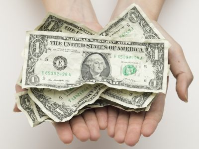 Dollar bills placed on top of the hand